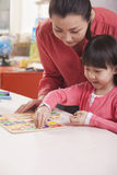 Teaching Helping Young Girl with Cut-Out Alphabet Letters Stock Photography