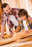 Teaching his son all about carpentry. Stock Photo