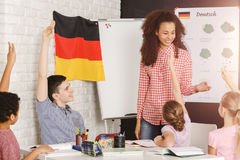 Teaching kids german. Happy teacher teaching young kids german words Stock Photography