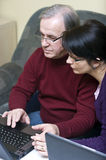 Teaching laptop usage. A woman (daughter) teaching a senior man (father) how to use a laptop. He has achieved his first success Stock Photos