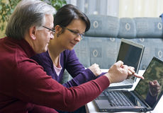 Teaching laptop usage. A woman (daughter) teaching a senior man (father) how to use a laptop. He has achieved his first success Stock Image