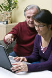 Teaching laptop usage. A woman (daughter) teaching a senior man (father) how to use a laptop. He has achieved his first success Stock Photo