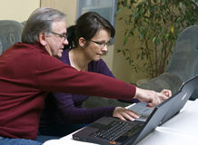 Teaching laptop usage. A woman (daughter) teaching a senior man (father) how to use a laptop. He has achieved his first success Royalty Free Stock Photos