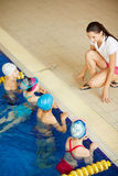 Teaching little swimmers. Young coach explaining rules of swimming to active cildren in pool Stock Photography