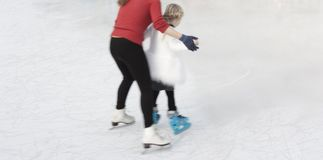 Teaching new skill ice skating to a chilld Stock Image