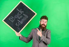 Teaching occupation demands talent and experience. Teacher welcomes students while holds chalkboard inscription back to stock images