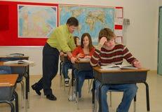 Teaching School Lessons. Three students in classroom, teacher helping teen girl Stock Photo