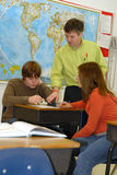 Teaching School Lessons. A teacher helps two students in classroom Royalty Free Stock Photos