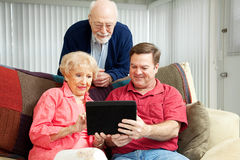 Teaching Seniors to Use Tablet PC. Adult son teaching his parents to use their new tablet pc Stock Image