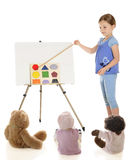Teaching About Shapes. A young elementary girl teaching her toys about shapes. On a white background stock photo