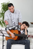 Teaching son how to play guitar. Royalty Free Stock Photo