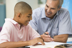 Teaching a Student. A smiling male teacher  explaining to an African American student Royalty Free Stock Image