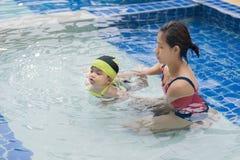 Teaching swim. Mom is teaching her daughter to swim in the pool royalty free stock photo