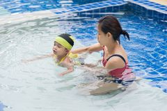 Teaching swim. Mom is teaching her daughter to swim in the pool royalty free stock photography