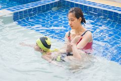 Teaching swim. Mom is teaching her daughter to swim in the pool stock images