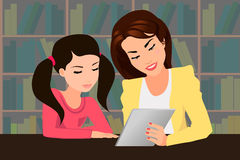 Teaching with a tablet PC. Teacher with her pupil in the library studying with a tablet PC Royalty Free Stock Photo