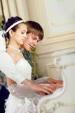 Teaching to play. Man teaching his bride to play the piano Stock Photo