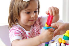 Teaching to use play dough. Hands of young woman show little girl how to use play dough Stock Photo