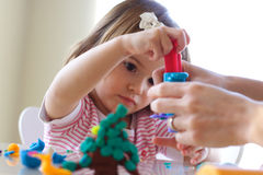 Teaching to use play dough. Hands of young woman show little girl how to use play dough Stock Images