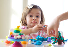 Teaching to use play dough. Hands of young woman show little girl how to use play dough Royalty Free Stock Photo
