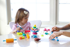 Teaching to use play dough. Hands of young woman show little girl how to use play dough Royalty Free Stock Photography