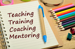 Teaching Training Coaching Mentoring words. On notebook Stock Photography