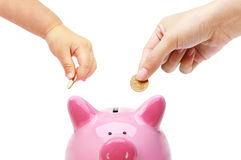 Teaching young kid to save money. Mother and a baby do saving money in a pink piggy bank / Teaching young kid to save money Royalty Free Stock Photography