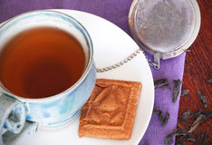 Teacup with black tea and a biscuit Royalty Free Stock Photo
