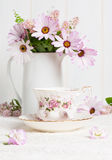 Teacup & Flowers. Floral teacup with jug filled with flowers stock photography