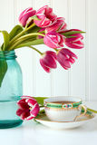 Teacup and flowers. Teacup and saucer with tulip flowers royalty free stock photos