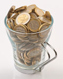 Teacup full of coins Stock Image