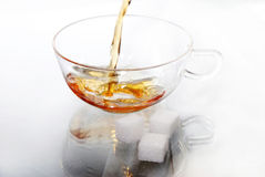 Teacup of glass with tea. Black tea is poured into a cup of glass, three pieces of sugar precede Royalty Free Stock Photo