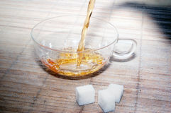 Teacup of glass with tea and three pieces of sugar Royalty Free Stock Images