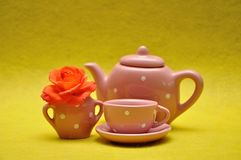 A teacup and a kettle with an orange rose royalty free stock photos