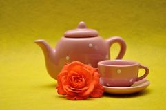 A teacup and a kettle with an orange rose. On a yellow background stock images