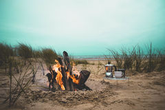 Teacup and Kettle Place Near a Burning Bonfire Under Blue Skies by the Beach Stock Photos