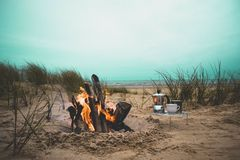 Teacup and Kettle Place Near a Burning Bonfire Under Blue Skies by the Beach Royalty Free Stock Image