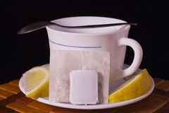 Teacup and lemon with tea and litle spoon Stock Photos