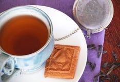 Teacup mit schwarzem Tee und einem Biskuit lizenzfreies stockfoto