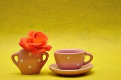 A teacup with an orange rose. On a yellow background stock photography