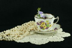 Teacup pearls and lace. Vintage teacup with lace and pearls stock photography