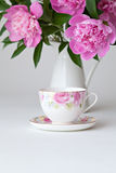 Teacup and pink peonies Stock Photography
