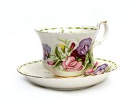 Teacup and Saucer with Sweet Peas. Bone China teacup with matching saucer in pinks, greens, purples, white and touch of yellow stock images