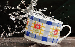 Teacup in a spray of water. Stock Photo