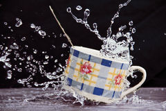 Teacup in a spray of water. Royalty Free Stock Photography