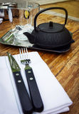 Teacup, teapot, fork and knife on a table in cafe Stock Photo