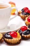 Teacup und fruchtiger Kuchen mit Biskuit stockfotos