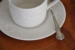 Teacup and Vintage Silverplate Teaspoon. A silverplate teaspoon rests with a teacup and saucer, awaiting tea, coffee, sugar and a quiet moment Stock Image