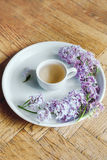 Teacup on the white plate. Lilac fresh flowers. Morning cup of tea and fresh lilac spring flowers stock photos