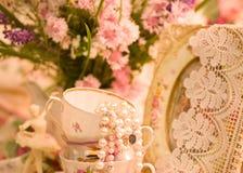 Teacups, ballet dancer statuette, frame. Vintage teacups, ballet dancer statuette, frame and flowers stock photos